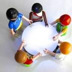 Playmobil-figuren stehen um einen Tisch und beraten sich